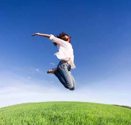 Happy woman jumping in green field against blue sky. Summer vacation concept
